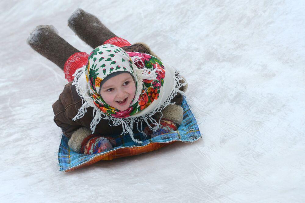 Dziewczynka zjeżdża z górki w pierwszy dzień Maslenicy w obwodzie archangielskim w Rosji.