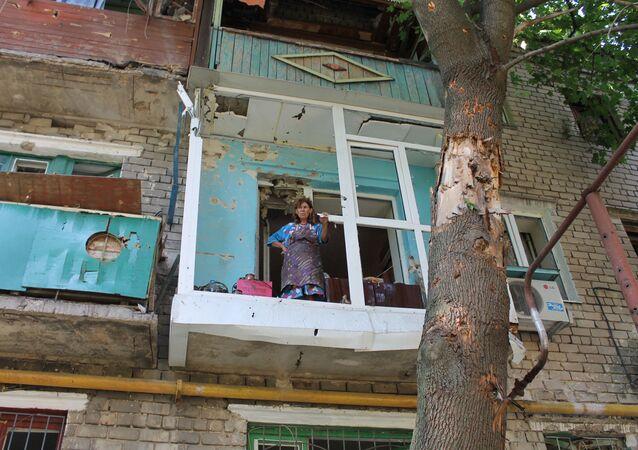 Kobieta na balkonie swojego mieszkania, zniszczonego podczas ostrzału przez ukraińską armię