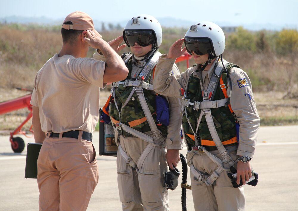 Rosyjscy piloci przyjmują raport od dowódcy techników przed lotem w bazie lotniczej Hmeimim w Syrii