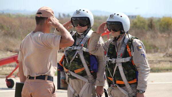 Rosyjscy piloci przyjmują raport od dowódcy techników przed lotem w bazie lotniczej Hmeimim w Syrii - Sputnik Polska
