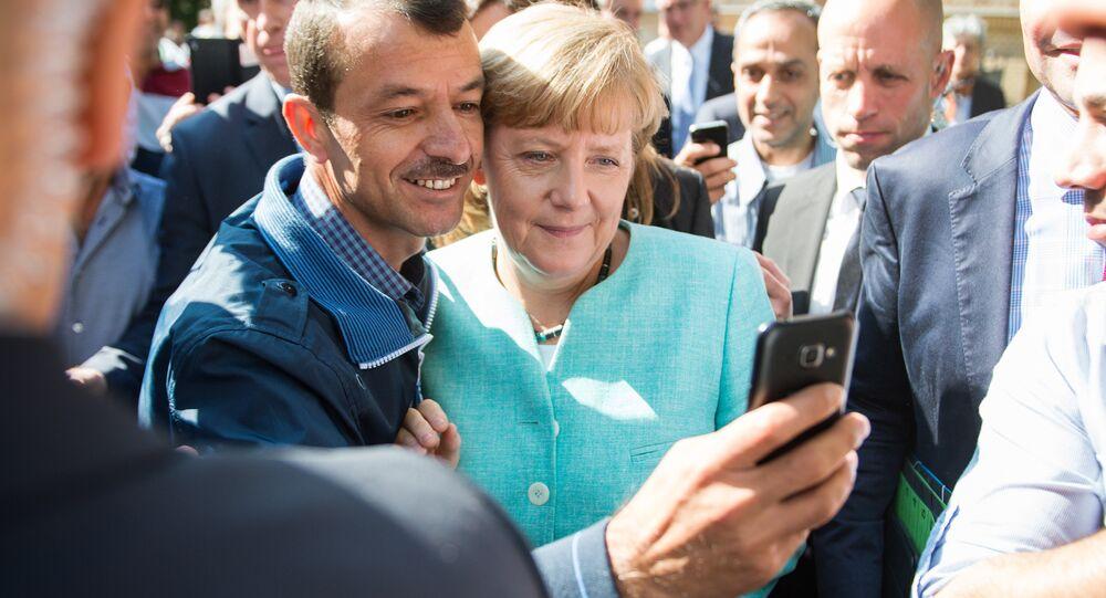 Angela Merkel fotografuje się z uchodźcą