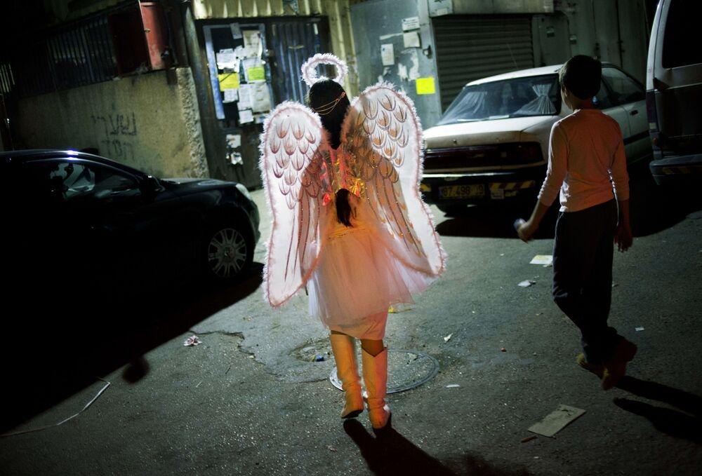 Dziewczynka w stroju anioła podczas obchodów święta Purim w Netanji, Izrael