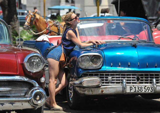 Dziewczyna pozuje przy samochodzie w Hawanie