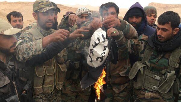 Syryjscy żołnierze palą flagę Państwa Islamskiego - Sputnik Polska
