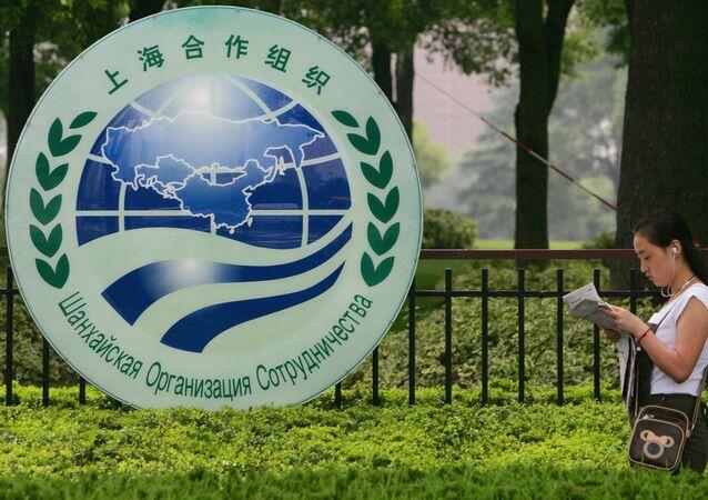 Kobieta przechodzi obok logo SOW w Szanghaju