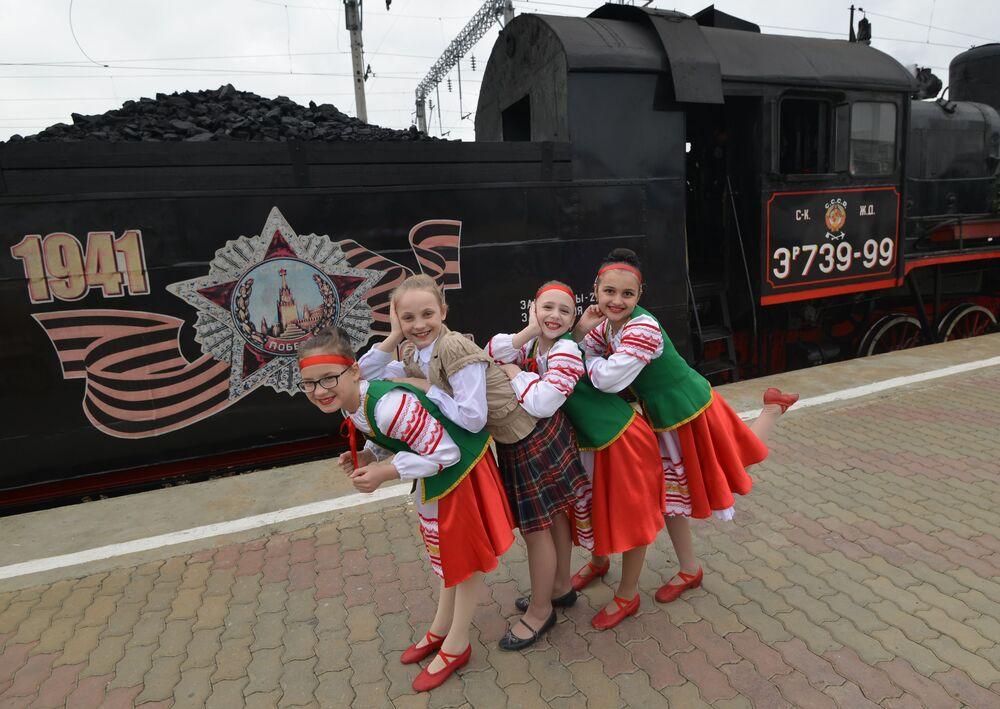 Dziewczynki w strojach ludowych podczas przyjazdu retro pociągu Pobieda na stację Mineralne Wody