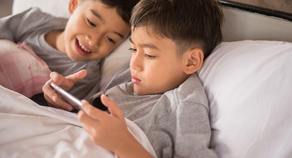 Сhłopcy bawią się smartfonem.