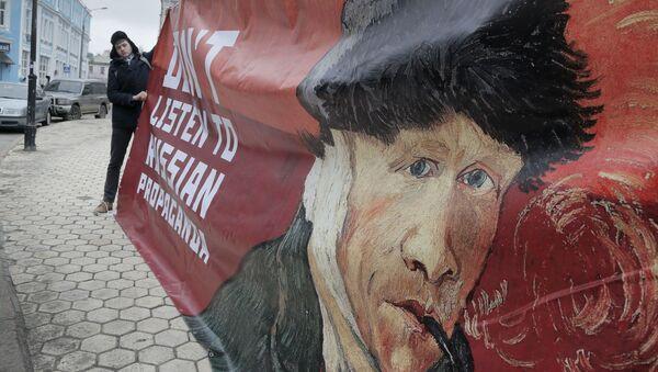 Kijowski aktywista z plakatem Nie słuchajcie rosyjskiej propagandy - Sputnik Polska
