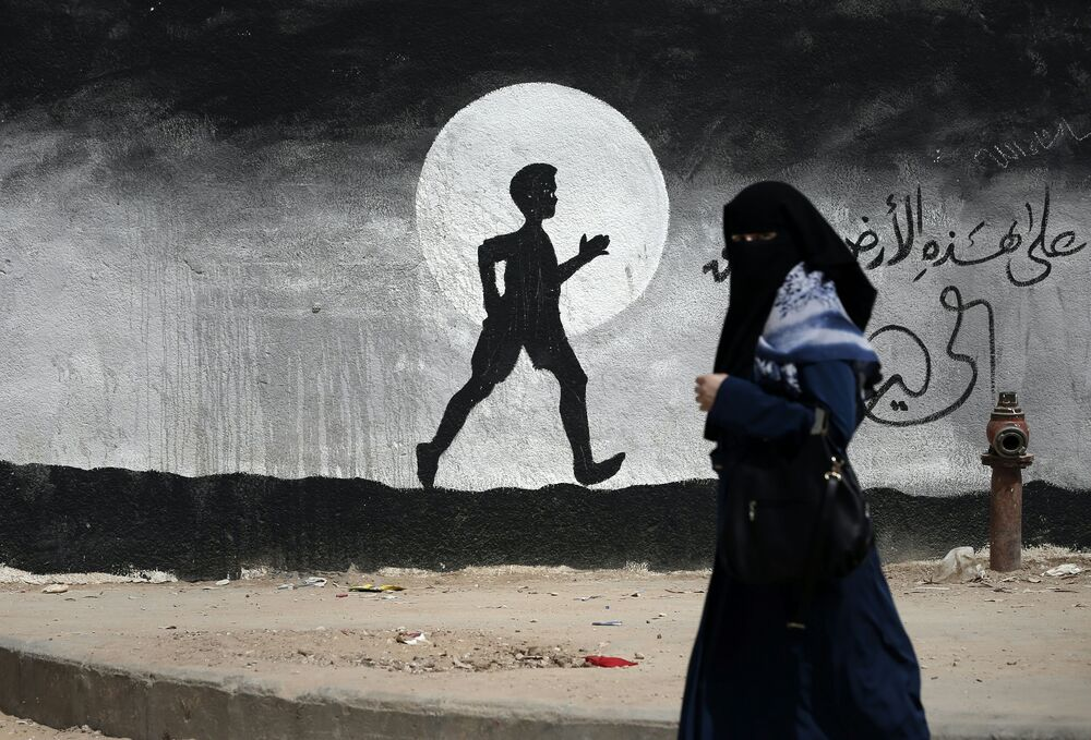 Palestynka przy ścianie z graffiti w Gazie