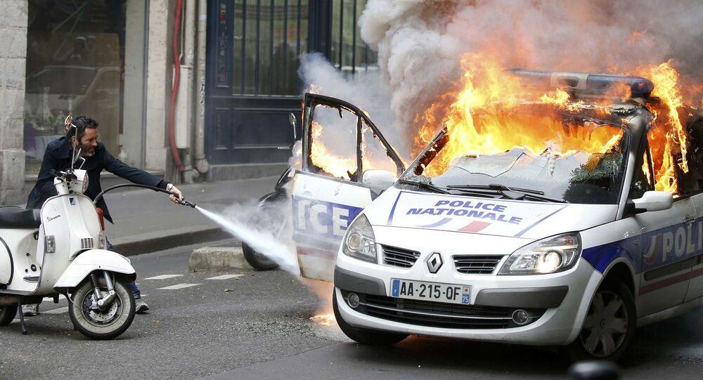 Mężczyzna próbuje ugasić wóz policyjny podczas zamieszek w Paryżu