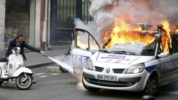Mężczyzna próbuje ugasić wóz policyjny podczas zamieszek w Paryżu - Sputnik Polska