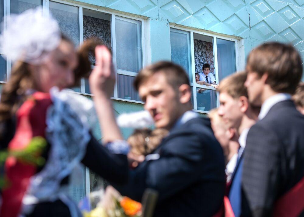 Uczniowie (na dalszym planie) obserwujący absolwentów świętujących zakończenie nauki w szkole im. A. Lupowa w mieście Tara (obwód omski).