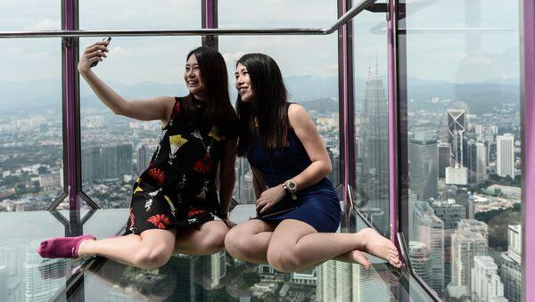 Dziewczyny z Malezji robią sobie zdjęcia w szklanym pomieszczeniu Sky Box na tle panoramicznego widoku z wieży telewizyjnej Manara Kuala Lumpur. - Sputnik Polska