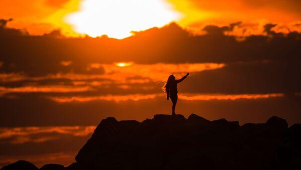 Dziewczyna robi sobie zdjęcie na promenadzie Olimpijskaja w Adlerze (Soczi) na tle zachodzącego słońca. - Sputnik Polska