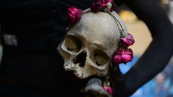 Mężczyżna trzyma czaszkę w ręku - Sputnik Polska