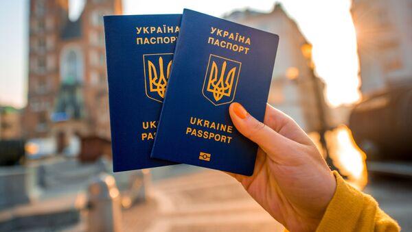 Женщина держит загранпаспорт для граждан Украины - Sputnik Polska