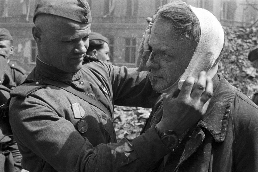 Radziecki żołnierz bandażuje rannego berlińczyka.