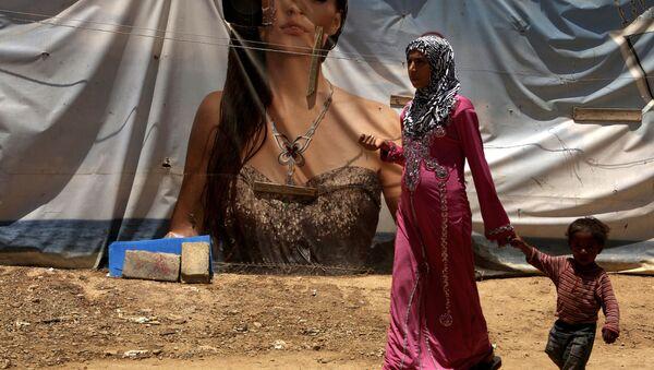 Syryjka z dzieckiem przechodzi naprzeciwko plakatu reklamowego w ośrodku dla uchodźców w Libanie - Sputnik Polska