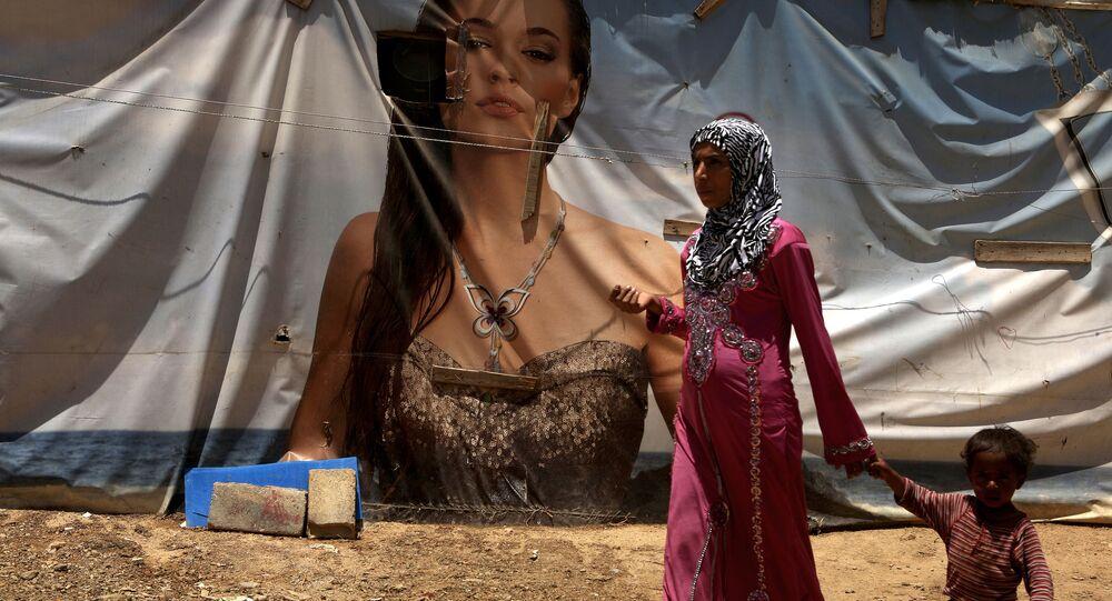 Syryjka z dzieckiem przechodzi naprzeciwko plakatu reklamowego w ośrodku dla uchodźców w Libanie