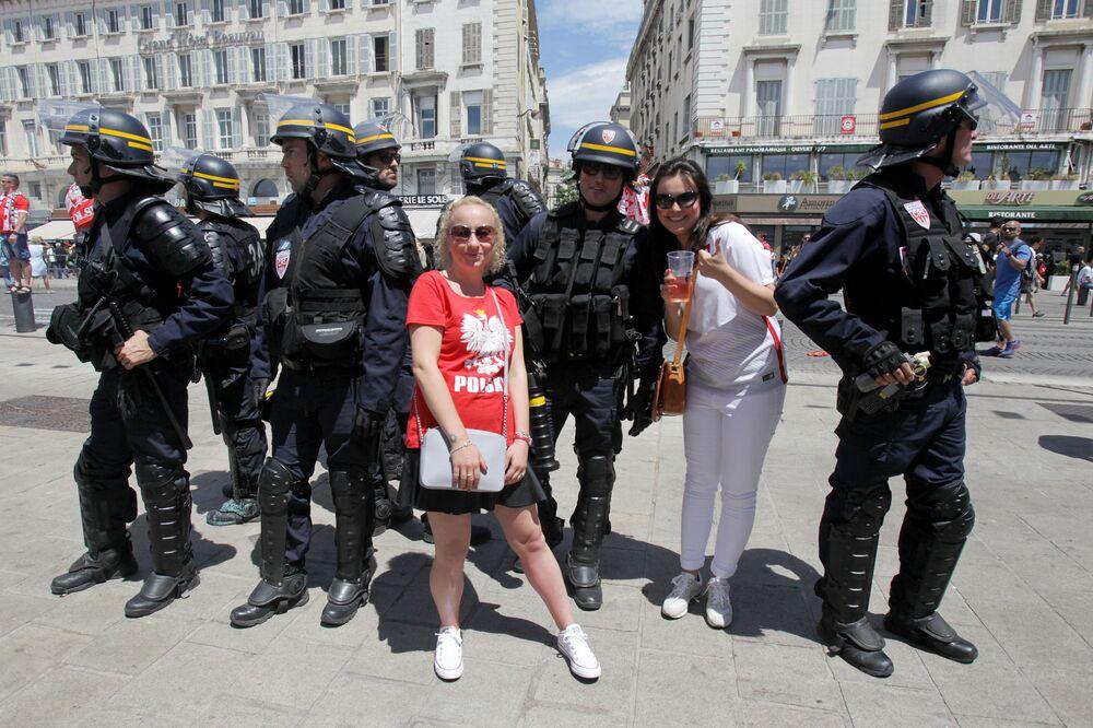 Polscy kibice robią zdjęcia z francuskimi policjantami  w Marsylii podczas Mistrzostw Europy w piłce nożnej.