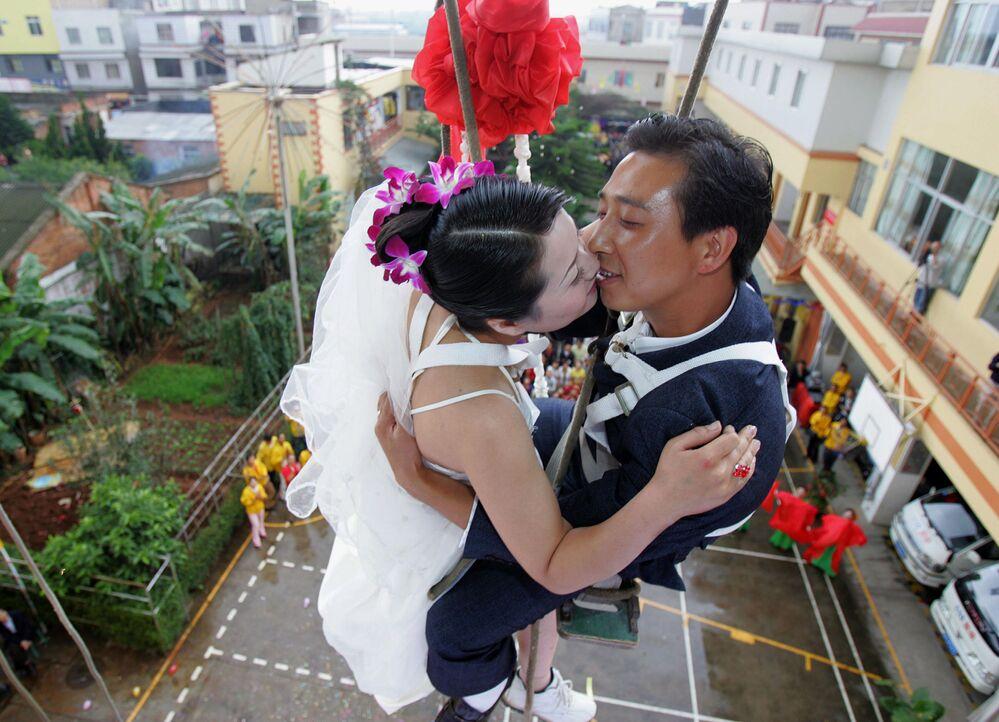 Para młoda w trakcie ceremonii ślubnej wisi między piętrami budynku w Chinach.