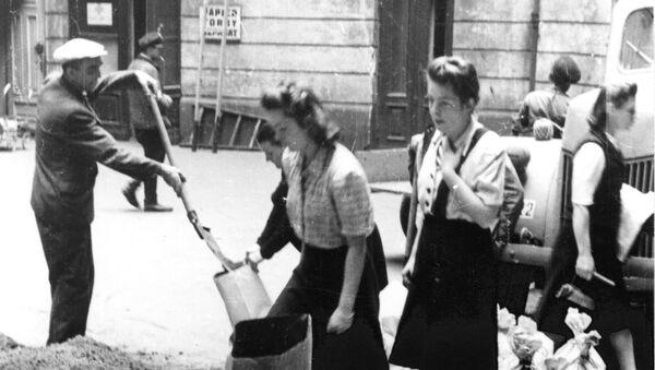 Mieszkańcy Warszawy napełniają worki z piaskiem w czasie Powstania Warszawskiego, 1944. - Sputnik Polska