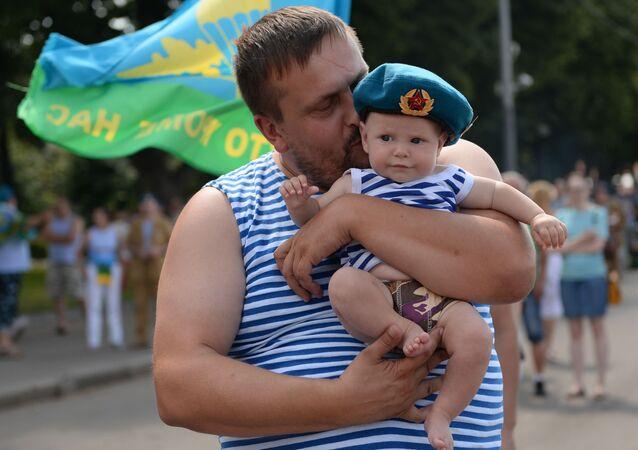 Żolnierz z dzieckiem podczas świętowania Dnia Wojsk Powietrzno-Desantowych w Parku Gorkiego w Moskwie.