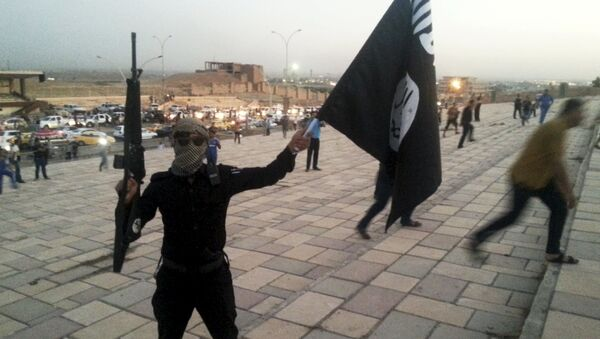 A fighter of Daesh, also known as ISIL, holds an ISIL flag and a weapon on a street in the city of Mosul, Iraq, in this June 23, 2014. - Sputnik Polska