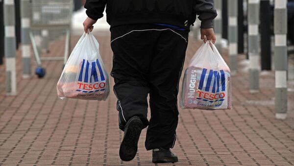 Mężczyzna z zakupami z supermarketu Tesco - Sputnik Polska