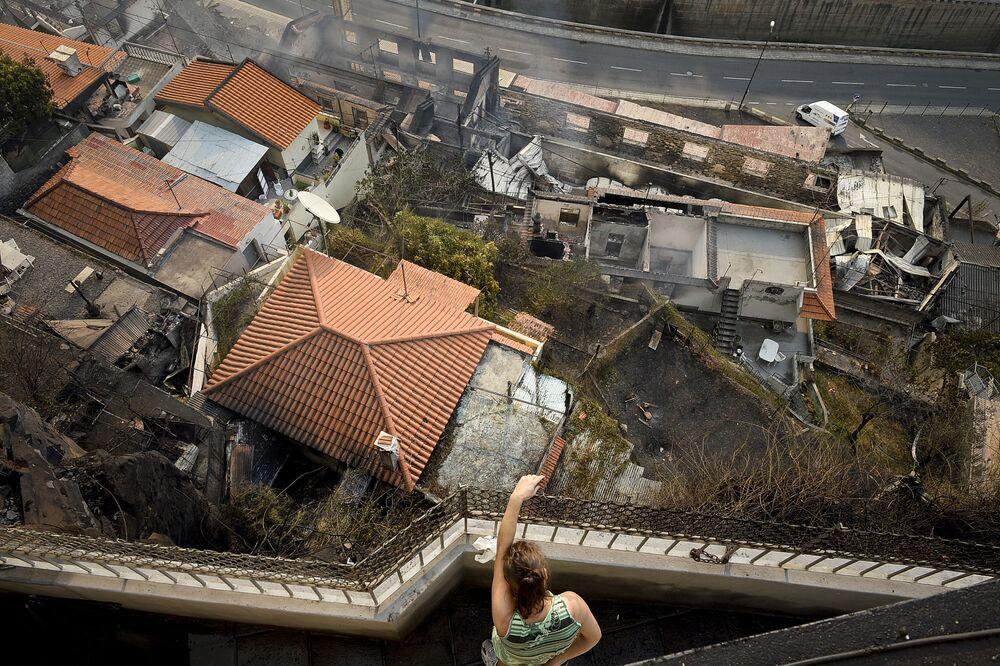 Kobieta patrzy z balkonu na spalony dom w mieście Funszal na wyspie Madera