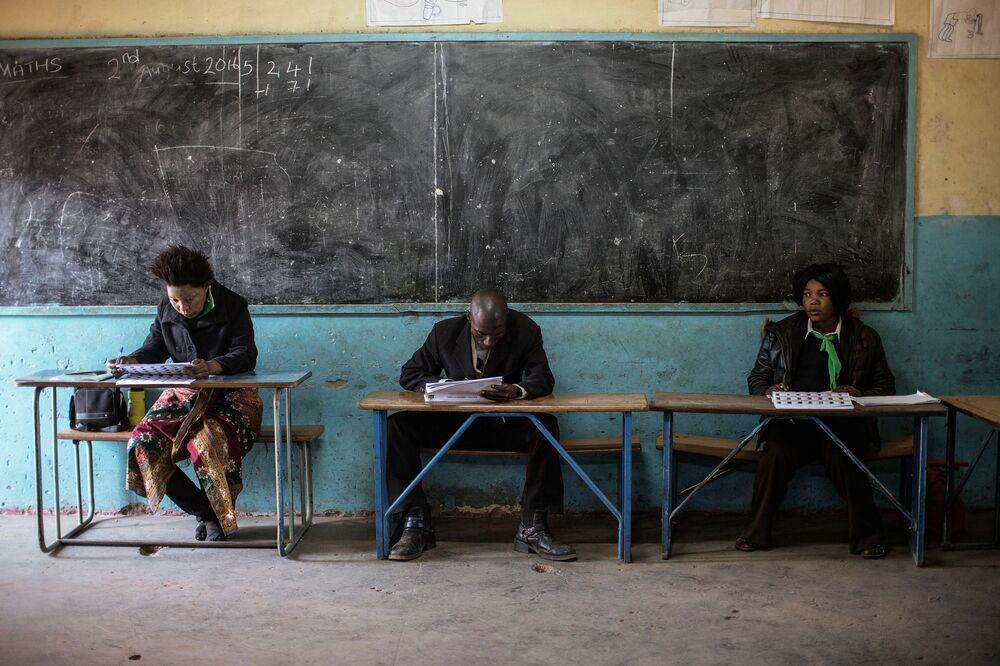 Agenci partii politycznych sprawdzają listy wyborcze podczas głosowania powszechnego w Zambii