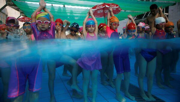 Dzieci na zajęciach na basenie w szkole pływania w Chinach. - Sputnik Polska