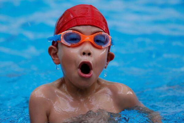 Chłopak pływa na basenie podczas zajęć w szkole pływania w Chinach. - Sputnik Polska