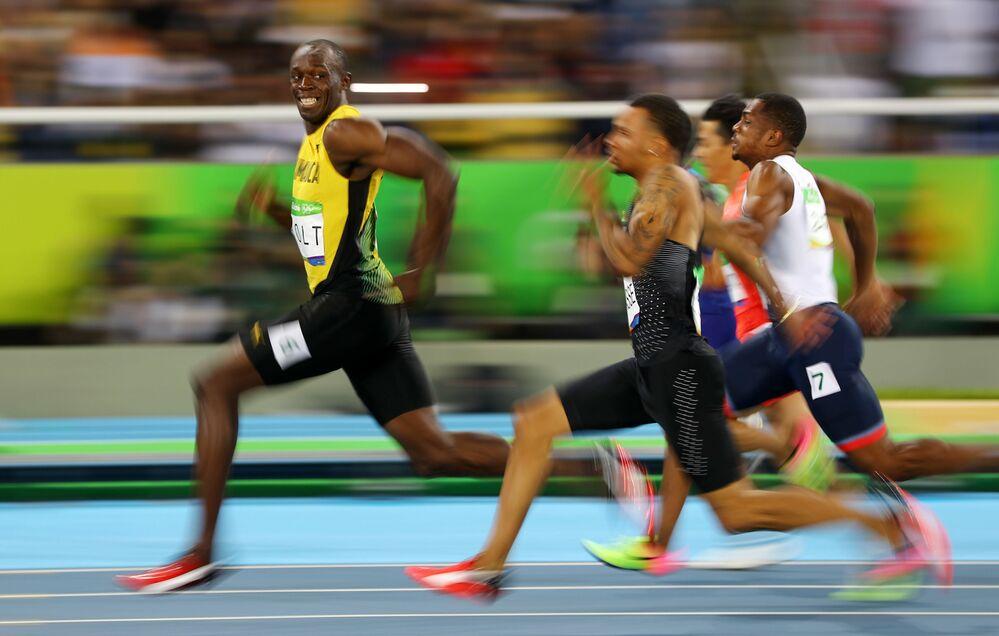 Jamajski biegacz Usain Bolt uśmiecha się do kamery podczas biegu na sto metrów na XXXI letnich Igrzyskach Olimpijskich