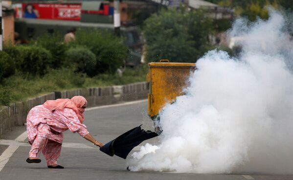 Kobieta próbuje zakryć pojemnik z gazem łzawiącym, rzucony  przez policję w protestujących przeciwko zabójstwom w Kaszmirze w indyjskim mieście Srinagar - Sputnik Polska