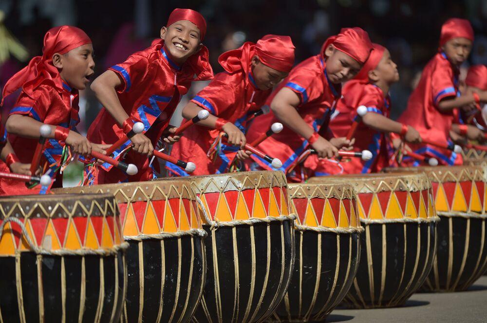 """Indonezyjscy chłopcy grają na narodowych instrumentach muzycznych """"dol"""" podczas świętowania Dnia Niepodległości Indonezji w Dżakarcie"""