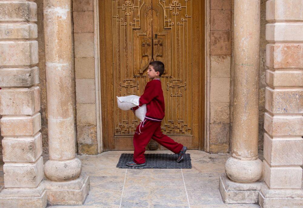 Chłopiec z workiem pomocy humanitarnej w chramie św. Marii ormiańskiej cerkwi apostolskiej w Latakii.