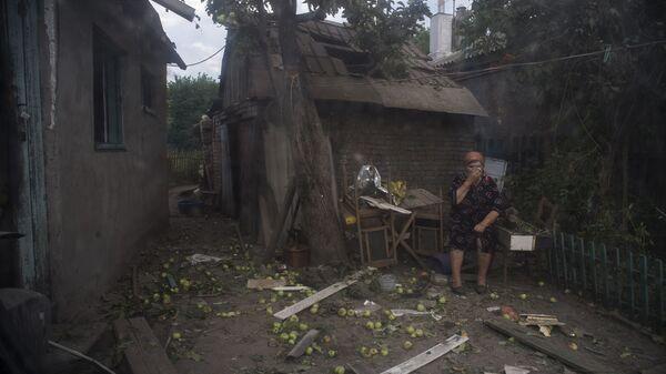 Mieszkanka Ługanska przed domem zniszczonym przez ostrzał artyleryjski miasta dokonany przez wojska ukraińskie - Sputnik Polska