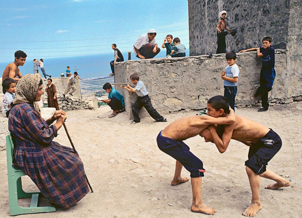 Dzieci grają na placu koło mogiły świętego Georgija w starym dagestańskim mieście Derbent