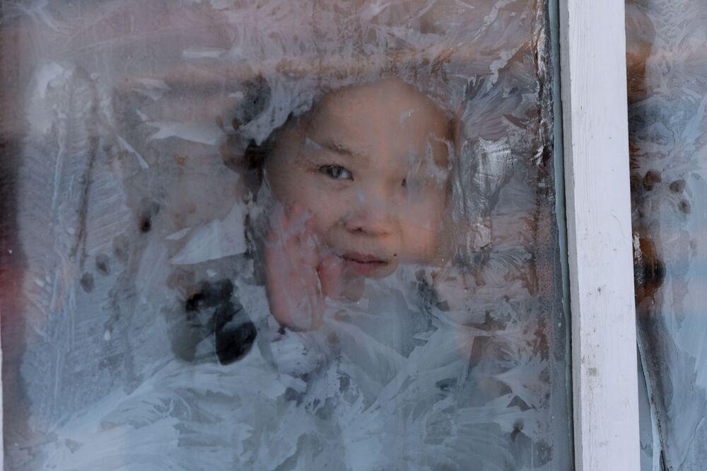 Dziewczyna w oknie domu na zimowym obozowisku w Republice Tywa