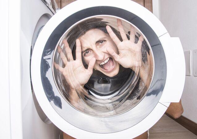 Kobieta patrzy przez drzwi pralki