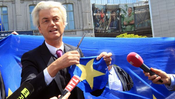 Duński populista i eurosceptyk Geert Wilders wycina gwiazdę z flagi UE tuż przed budynkiem Parlamentu Europejskiego w Brukseli - Sputnik Polska