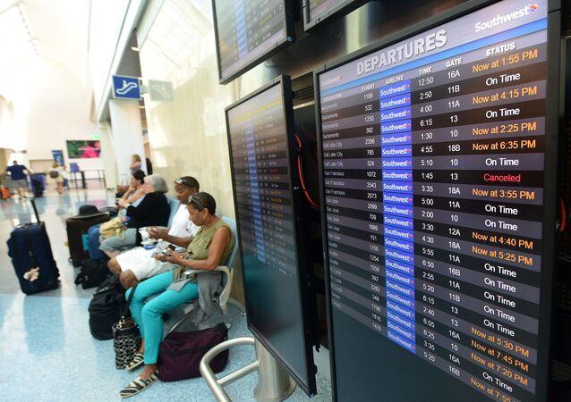 Pasażerowie i tablica na lotnisku w Los Angeles, USA