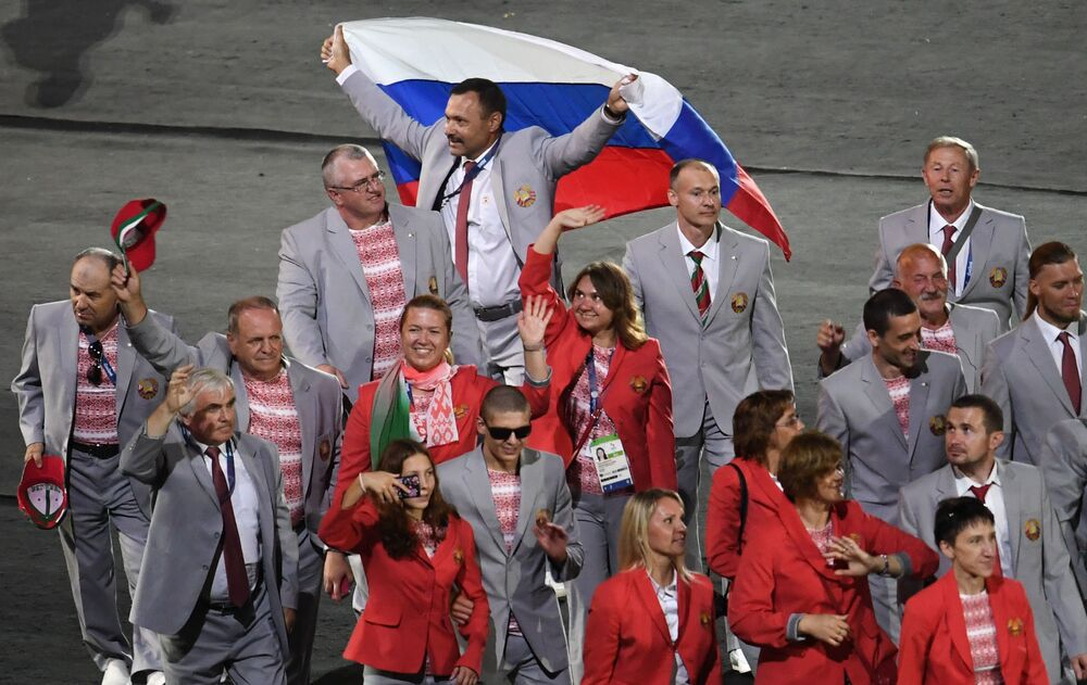 Przedstawiciel białoruskiej delegacjiAndriej Fomoczkin z flagą Rosji podczas parady atletów i członków reprezentacji narodowych na ceremonii otwarcia XV letnich Igrzysk Paraolimpijskich 2016 w Rio de Janeiro