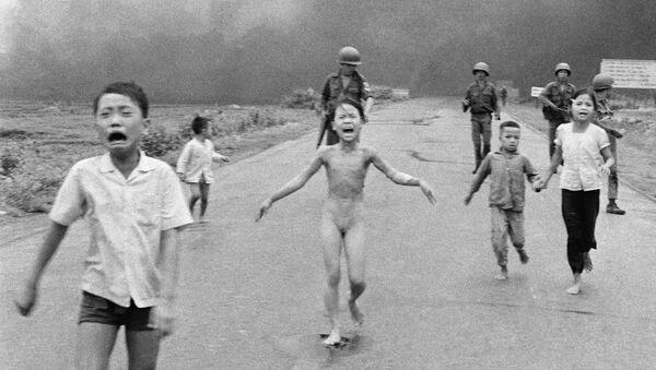 """""""Napalmowa dziewczynka"""" to kultowe zdjęcie Nicka Uta, fotoreportera Associated Press, za które w 1973 roku otrzymał on Pulitzera. W 1972 roku lotnictwo południowokoreańskie przez pomyłkę zrzuciło napalm na ludność cywilną. Bohaterka zdjęcia, Kim Phúc, została poważnie poparzona. Później stała się symbolem okrucieństwa wojny w Wietnamie - Sputnik Polska"""