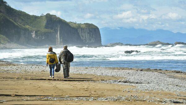 Turyści na brzegu Morza Ochockiego w zachodniej części wyspy Kunaszir. - Sputnik Polska