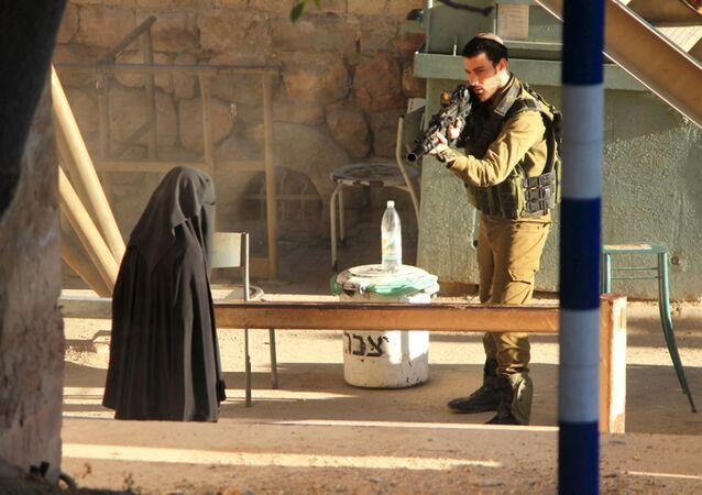 Izraelski żołnierz celuje w Palestynkę na punkcie kontrolnym w Hebronie