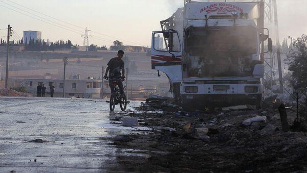 Zniszczona w wyniku pożaru ciężarówka z pomocą humanitarną w rejonie Urm al-Kubry na zachodnich peryferiach Aleppo - Sputnik Polska