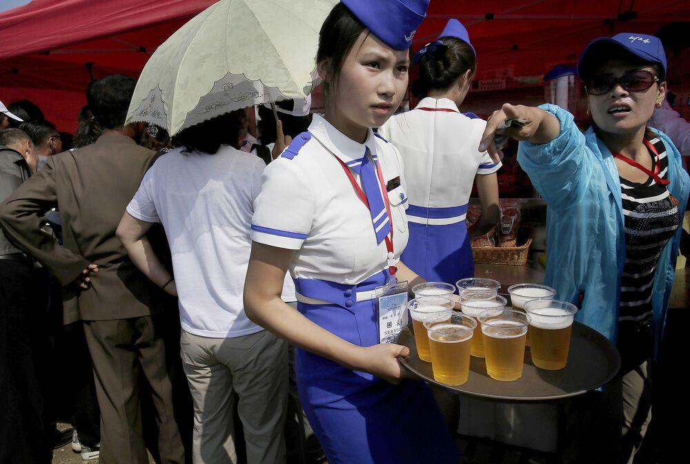 """Kelnerka podczas pokazów lotniczych """"Festiwal Lotniczy Przyjaźni Narodów"""" w Korei Północnej"""