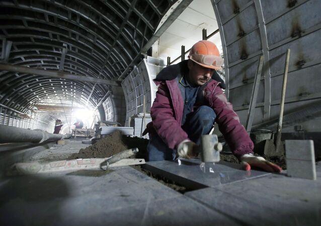 Pracownik układa płytki na przyszłym peronie moskiewskiego metra